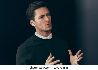Serious young handsome man have a conversation with colleagues during meeting on black background, with wireless earphones. Caucasian businessman using wireless headphones in business conference.