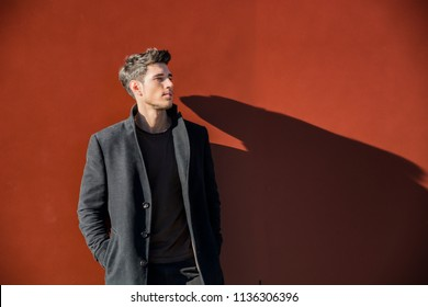 Serious Young Handsome Man in Winter Outfit Leaning on a Red Metal Wall While Looking to a Side of the Frame at Large Copyspace