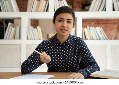 Serious young indian female sit at desk with books and papers talk to camera shoot online training course, concentrated ethnic girl blogger or coach make video speak on live tutorial explain notions