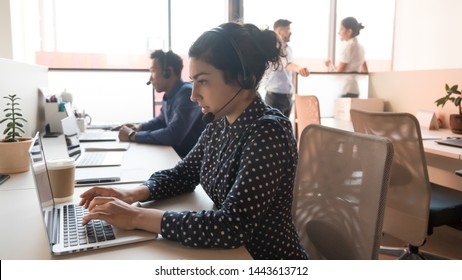 Serious young indian woman call center telesales agent operator telemarketer wear wireless headset work with team using computer in customer care service support helpline helpdesk multiethnic office