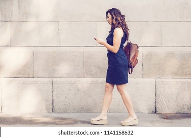 Serious young Latin-American female tourist wearing dress walking on sidewalk along wall, carrying bag and using mobile phone