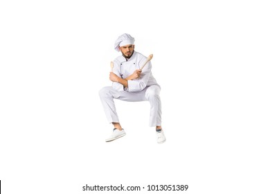 serious young male chef with utensils jumping and looking at camera isolated on white
