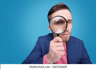 Serious young male detective holding magnifying glass by right eye while standing in front of camera in isolation