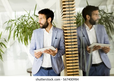 Serious young male executive using digital tablet