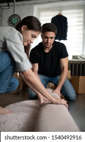 Serious young male helping woman to unroll soft carpet while sitting on floor during relocation in new apartment