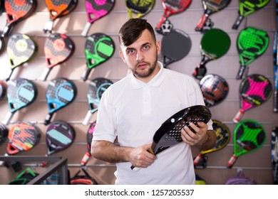 Serious young male looking for new padel racquet in store of sports equipment