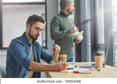 Serious young male worker concentrated on documents as prepares report, has lunch break, eats fresh vegetable salad, sits at wooden table with laptop computer and thoughtful partner eats chineses food