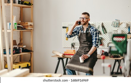 Serious young man in apron with cup of takeaway coffee in hand talking on smartphone while leaning on workbench in modern workshop