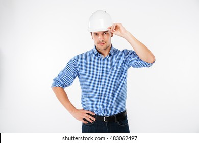 Serious young man building engineer in hard hat standing and posing