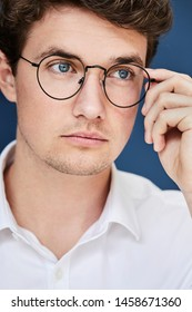 Serious young man in glasses, looking away