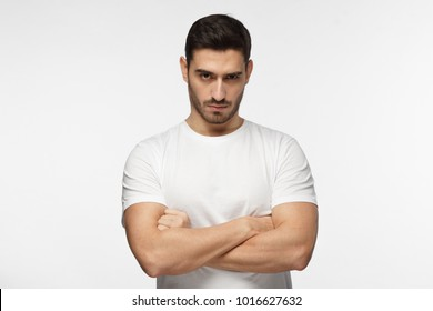 Serious young man portrait. Tough guy standing with crossed arms isolated on grey background