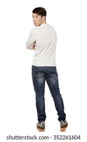 serious young man posing in jeans from the back
