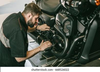 Serious young man repairing his motorcycle in bike repair shop. Mechanic fixing motocycle engine