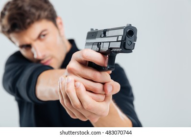 Serious young man standing and aiming with gun