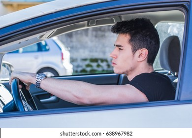 Serious young man or teenager driving car and looking at camera