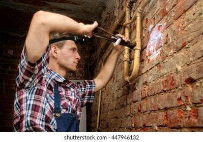 Serious young man wearing headlight fixing a leak with a pipe wrench in basement