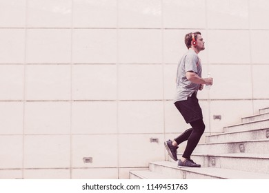 Serious young man wearing sportswear, listening to music and running upstairs on city stairs. Side view.