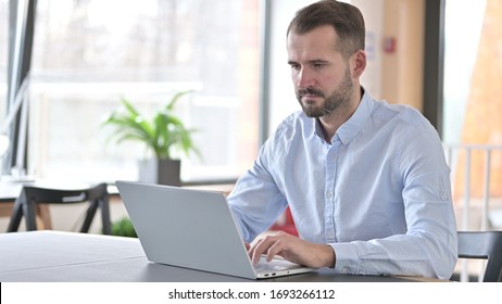 Serious Young Man Working on Laptop in Office