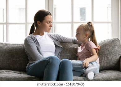 Serious young mom or nanny sit on couch with little preschooler girl talk sharing secrets, focused mother have conversation with small daughter, lecture or scold child, children upbringing concept