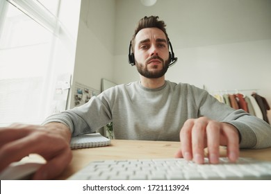 Serious young operator with headset looking at laptop display while sitting by table and consulting clients online in home environment