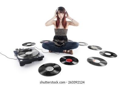 Serious Young Pretty Woman Sitting on the Floor Listening Music on a Vinyl Turntable with Vinyl Records Scattered on the Sides. Isolated on White Background.