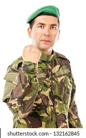 Serious young soldier with arm raised showing his fist isolated on white background