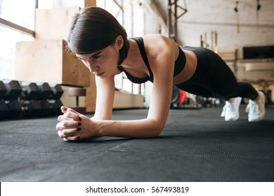 Serious young sportswoman doing plank exercise in gym