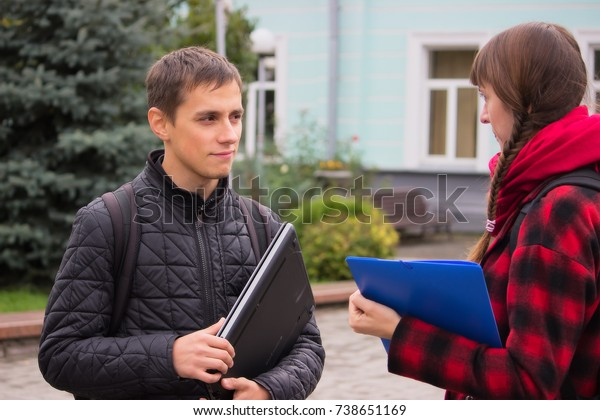 Serious young student friends talking at college