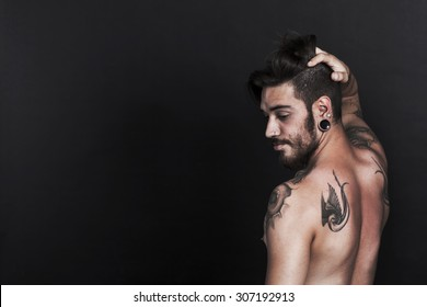 Serious young urban man with tattoo looking sideways with black background
