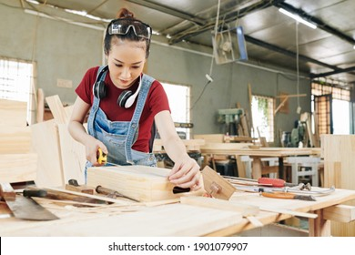 Serious young Vietnamese female carpenter in denim overall measuring wooden drawer she made for customer