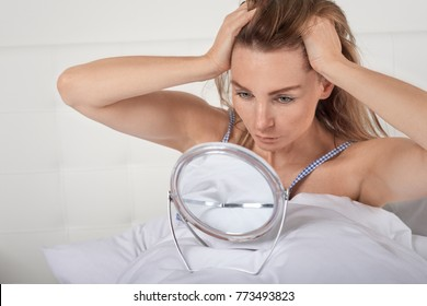 Serious young woman in bed looking at herself in a small portable hand mirror balanced on the bedclothes holding back her long hair with her hands