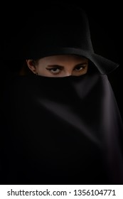 serious young woman in black hat cover her face with veil in dark looking at camera