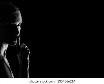 serious young woman with finger on her lips show silence gesture on black background with copy space looking at camera, monochrome