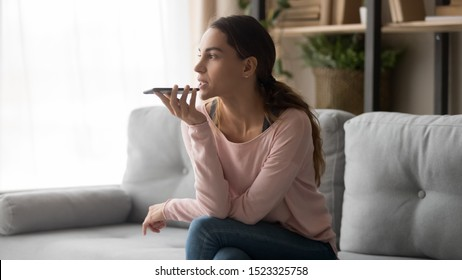 Serious young woman holding phone using mobile voice recognition or digital assistance app speak activate virtual assistant, record message or talk on speakerphone on smartphone sit on sofa at home