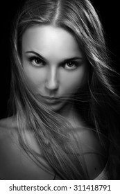 serious young woman looking at camera in dark monochrome