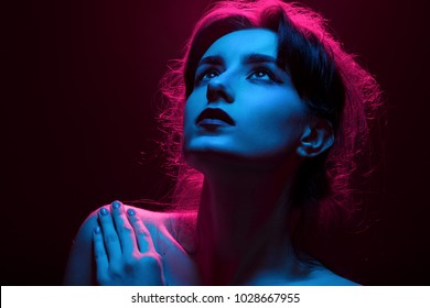 serious young woman in multicolor lights on black background looking up