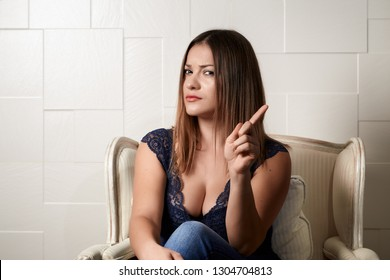 Serious young woman nagging someone, wagging her finger. Beautiful woman with big breasts seated on an armchair.