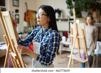 Serious young woman painting at art studio