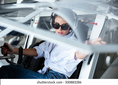 Serious young woman pilot in headset sitting in small plane