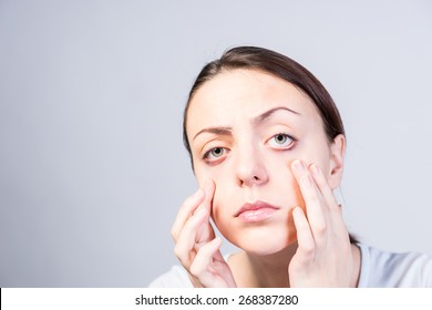 Serious Young Woman Pulling Down her Two Lower Eyelids with Both Hands While Looking at the Camera. Captured in Studio on a Light Gray Background with Copy Space.
