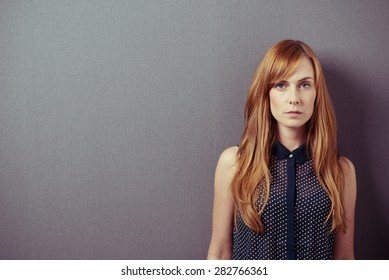 Serious Young Woman in Sleeveless Shirt, with Long Blond Hair, Against Gray Wall Background with Copy Space and Looking at the Camera.