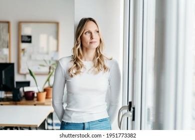 Serious young woman standing deep in thought looking through a window in a high key office with copyspace looking up with a contemplative expression