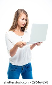 Serious young woman standing and using laptop isolated on a white background