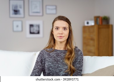 Serious young woman wearing gray sweater and long brown hair with blank stare while sitting on sofa with picture frames in background