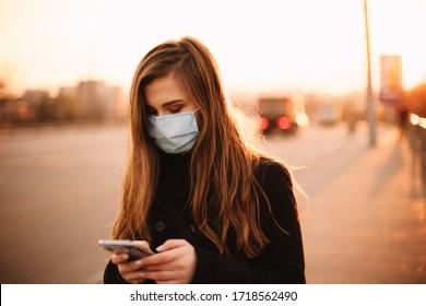 Mujer joven seria usando mascarilla médica protectora usando smartphone mientras caminaba por una acera vacía en la ciudad al atardecer
