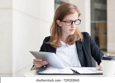 Serious Young Woman Working With Documents in Cafe