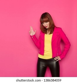 Serious young woman in yellow shirt, pink jacket and black leather trousers is showing pistol hand sign. Three quarter length studio shot on pink background.
