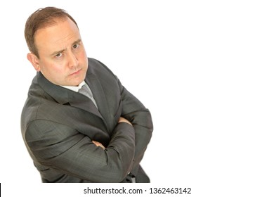 A serious-looking, concerned business manager with folded arms on a white background with copy space.