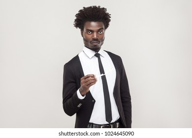 Seriously afro businessman looking at camera and wait. Studio shot