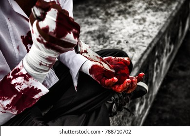 seriously injured man body wraps bandages bleeding in depression from unrequited love. use a knife smeared with blood stabbing a red heart in hand. love concept for valentine's day. in dark tone.